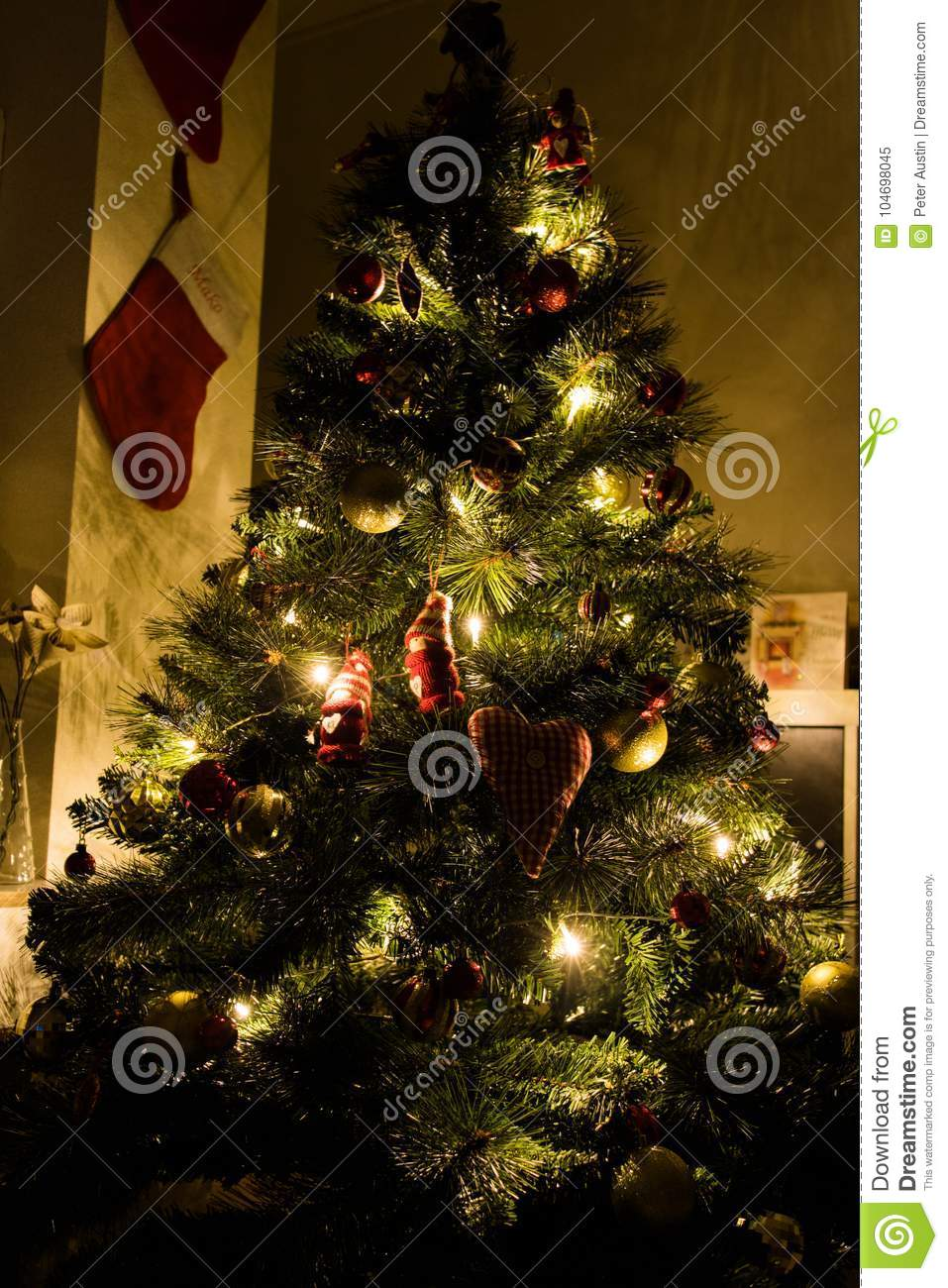 a beautiful christmas tree lit up in a small cosy room with stockings on the wall
