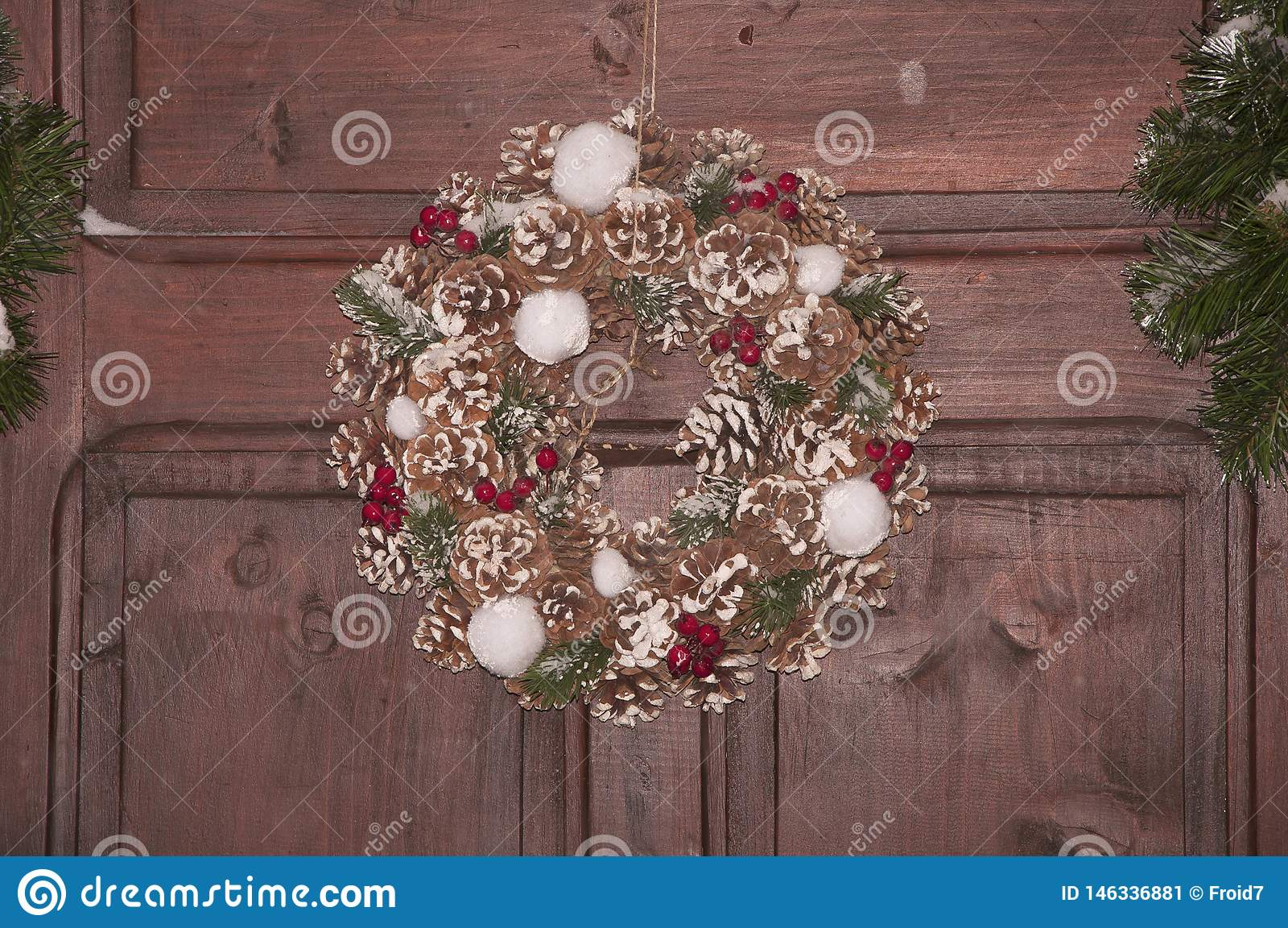 Beautiful Christmas wreath with green conifer, cones and berries. New Year decoration on brown background
