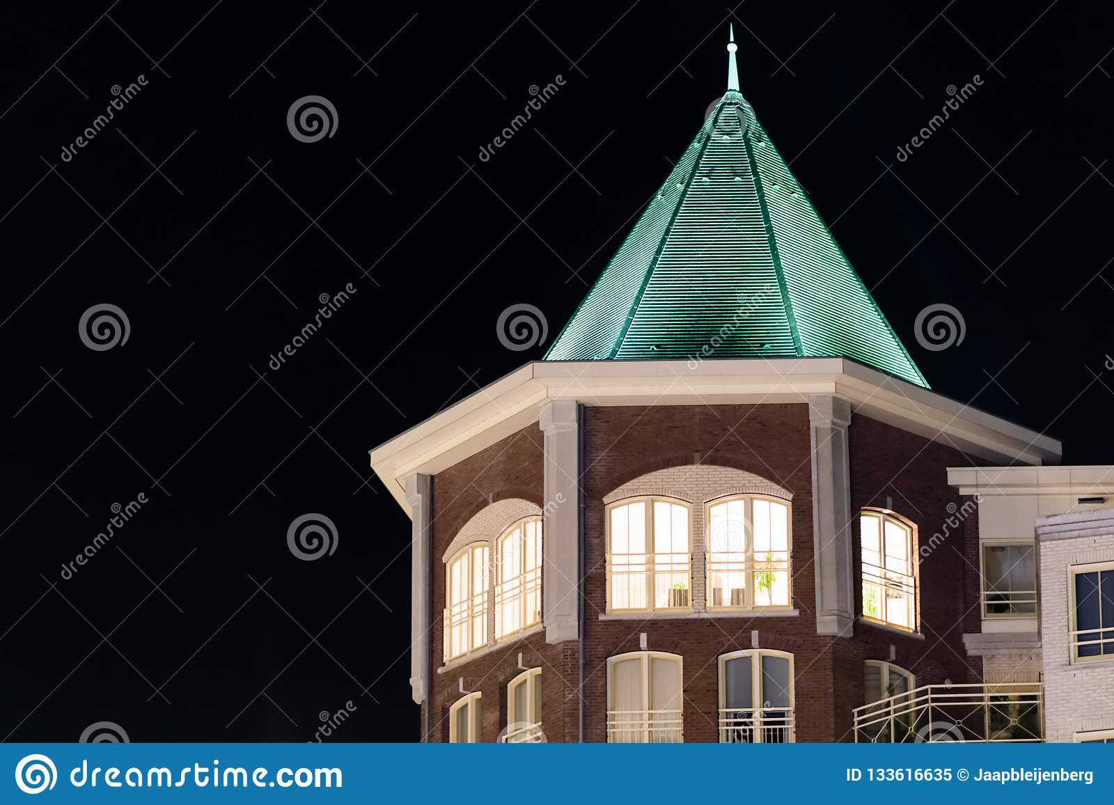 Beautiful city tower building with lighted apartment windows and a pointy rooftop, modern dutch architecture at night