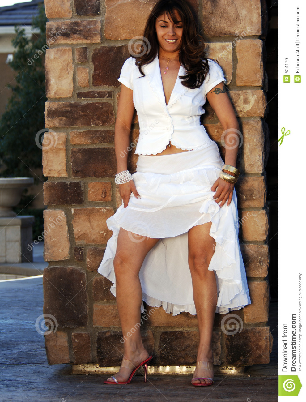 Latin Woman In White Dress Showing Off Her Legs