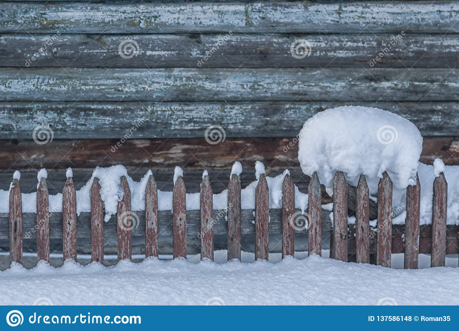 Beautiful clump of snow on a wooden fence with a snowy backdrop. There is a beautiful wooden palisade ahead. Christmas