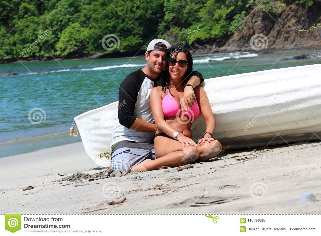 Beautiful couple at the beach with a boat, happy expressions gorgeous woman and latin guy at Costa Rica.