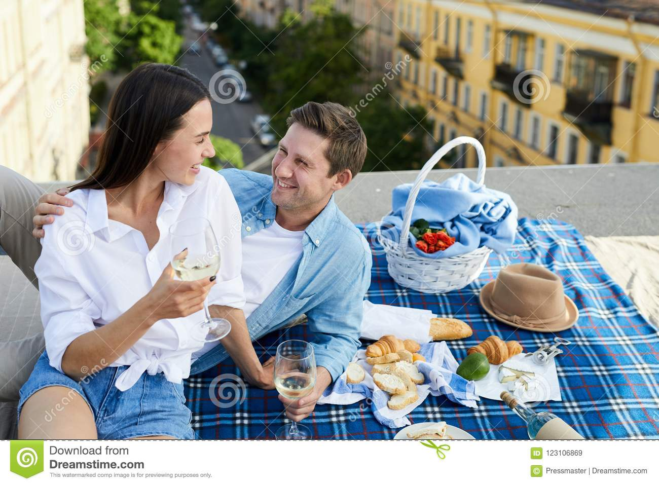 Beautiful couple chatting and laughing on roof