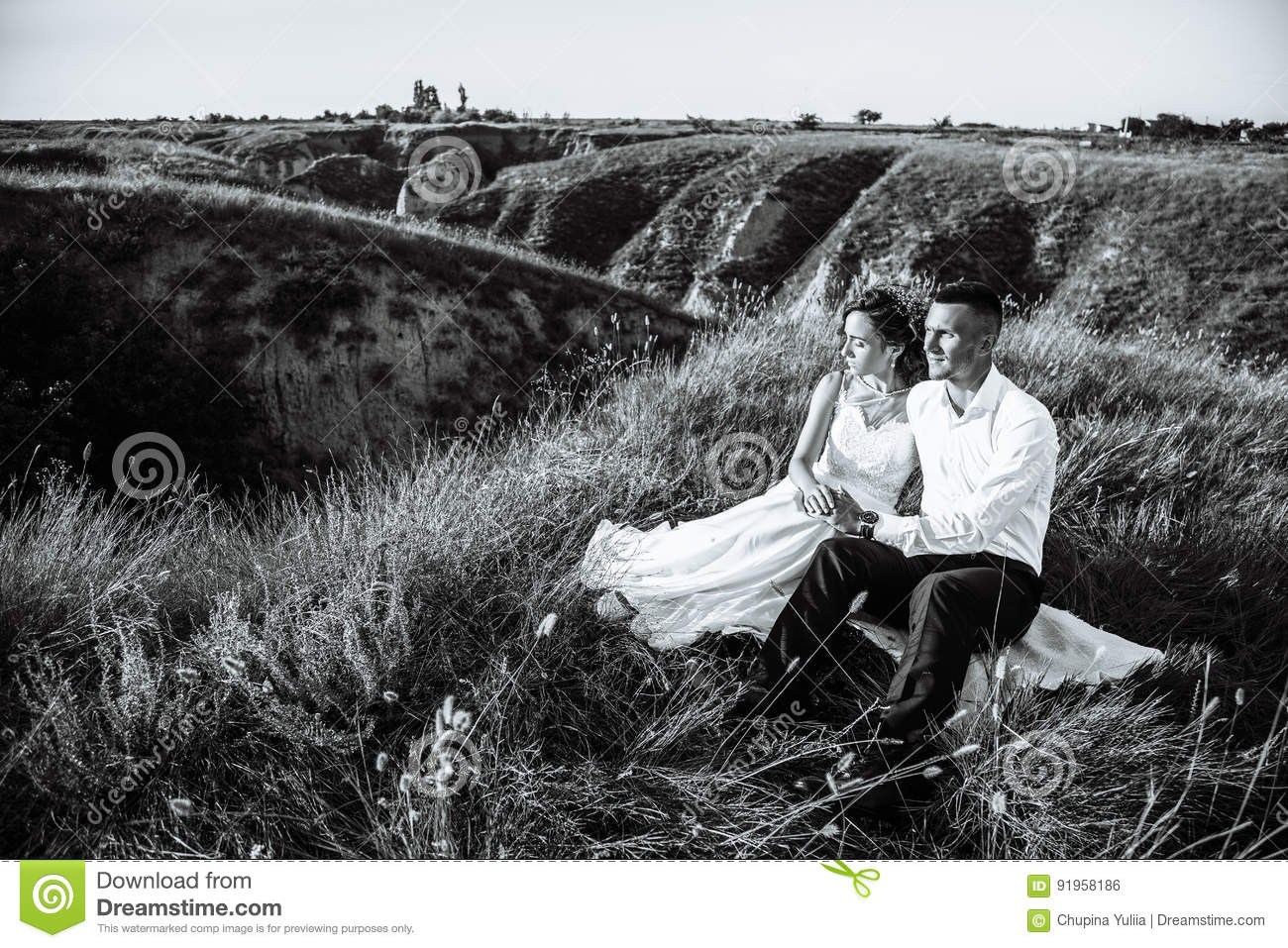 Beautiful couple in field lovers or newlywed posing on sunset with perfect sky real emotions black and white