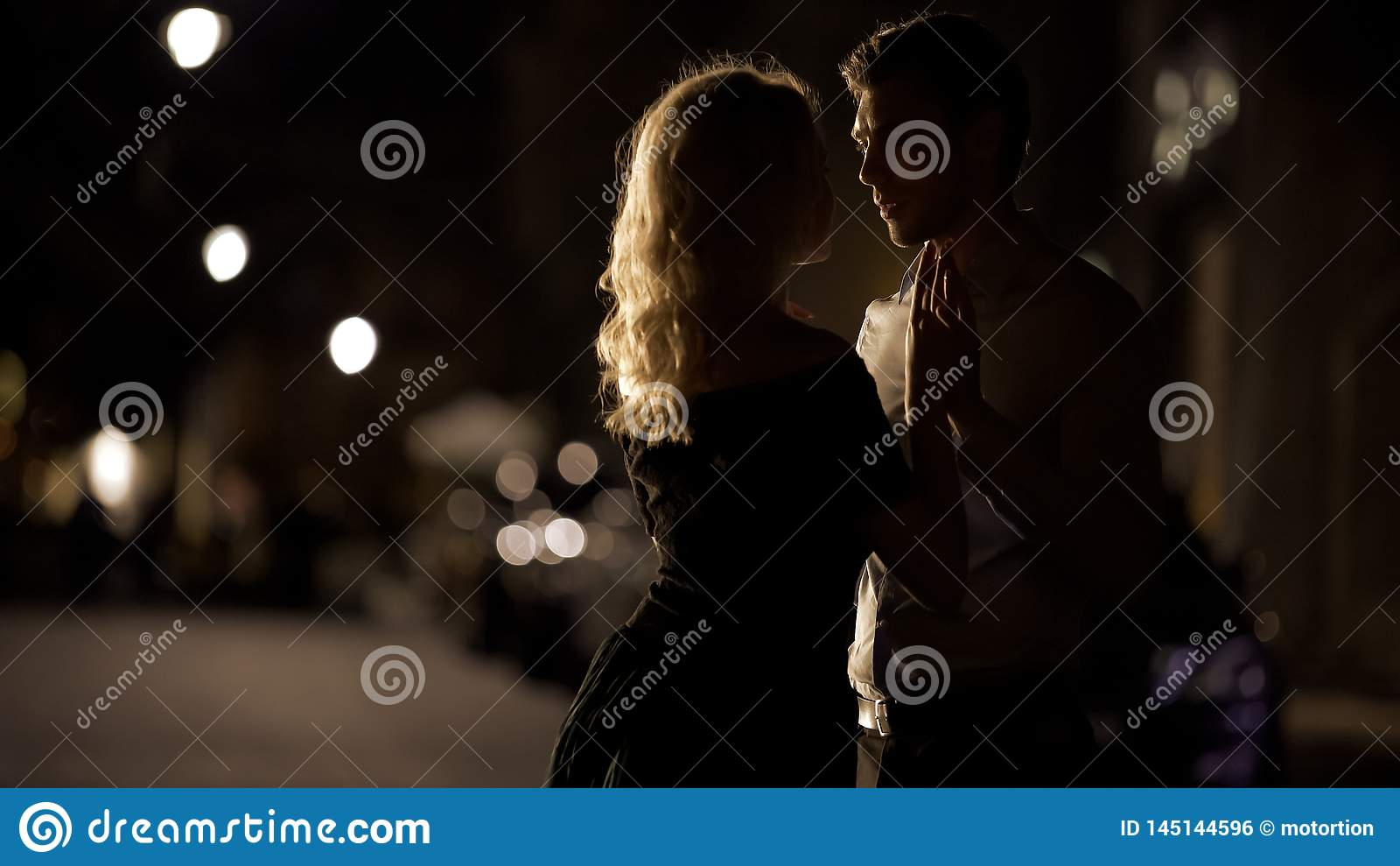 Beautiful couple holding hands and approaching to kiss, romantic date, love