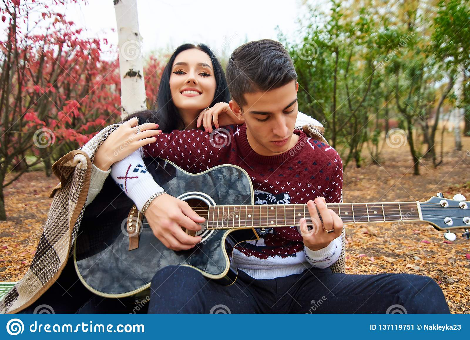 Beautiful couple in love on nature with a guitar