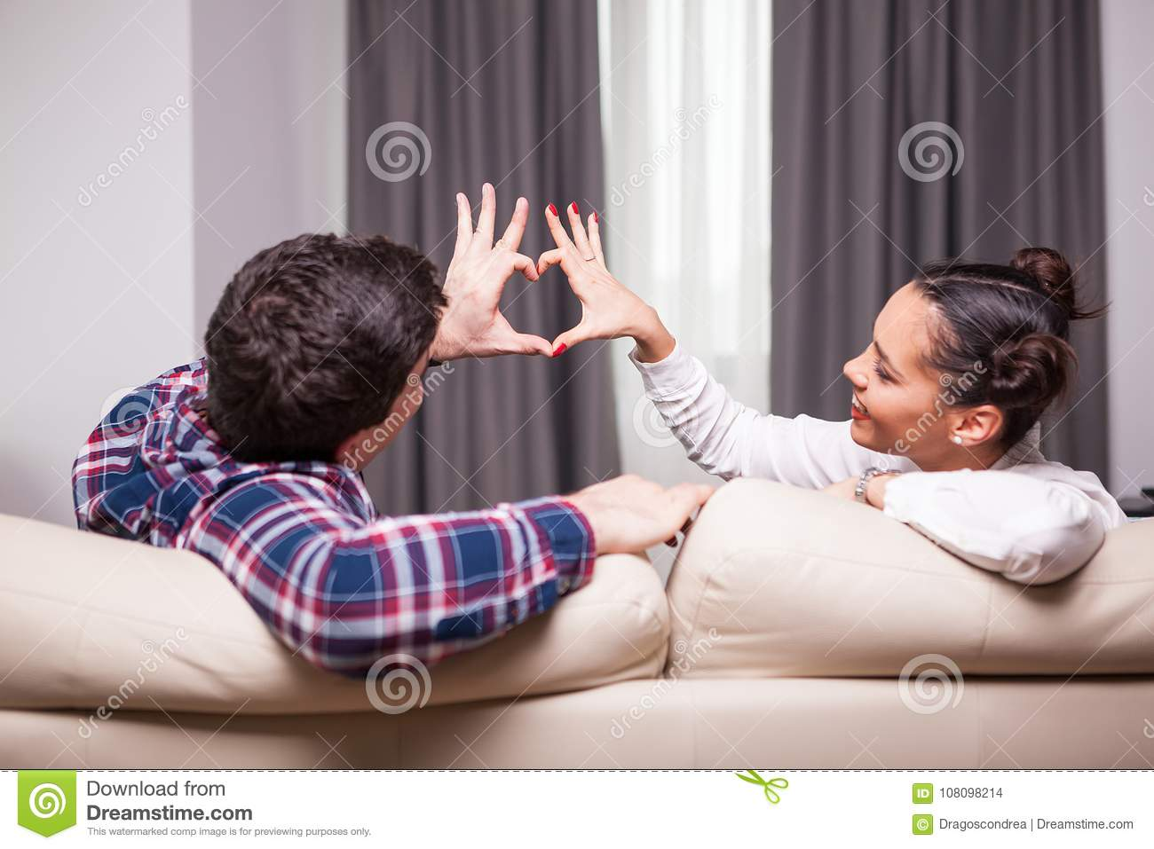 Beautiful couple making a heart shape from their fingers