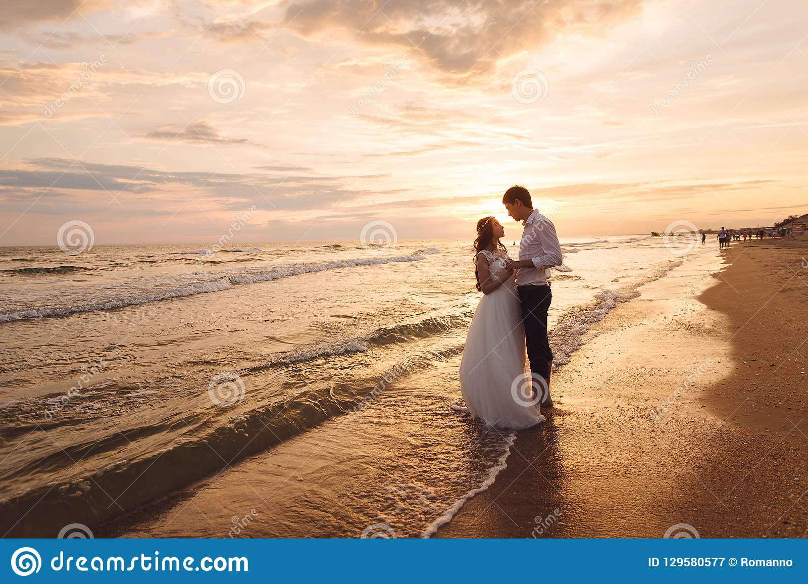 A beautiful couple of newlyweds, the bride and groom walking on the beach. Gorgeous sunset and sky. Wedding dresses, a