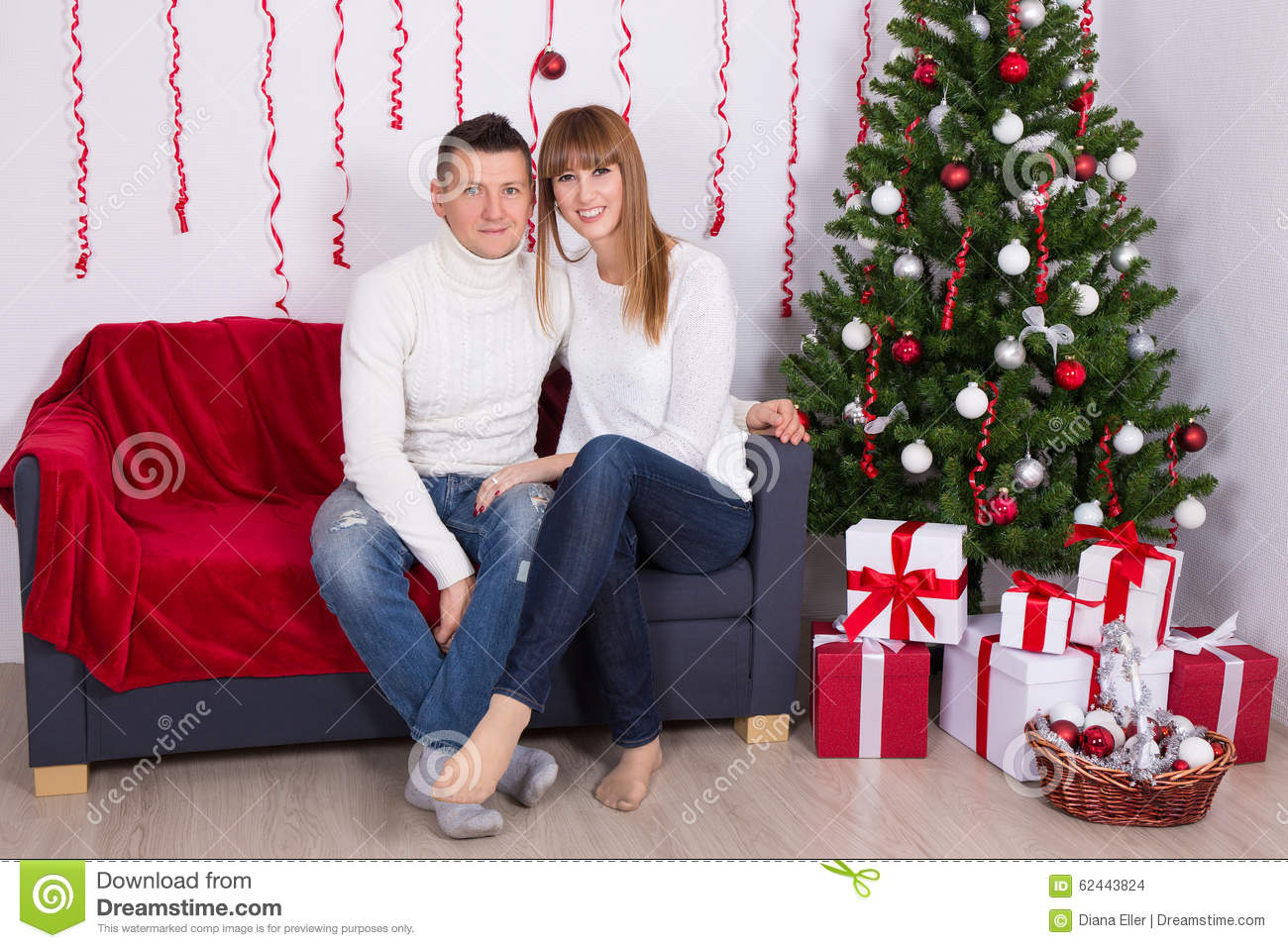 Beautiful couple sitting in decorated living room with for Living room ideas young couples