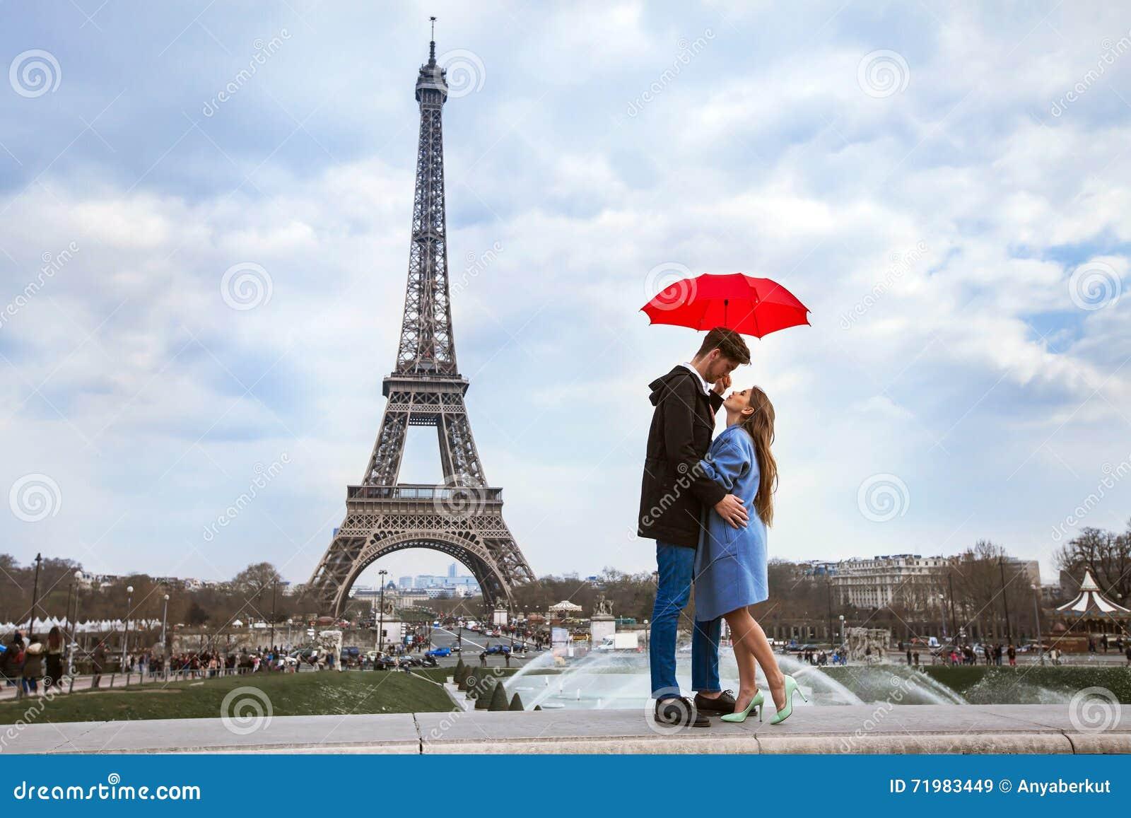 Beautiful couple with umbrella near Eiffel Tower