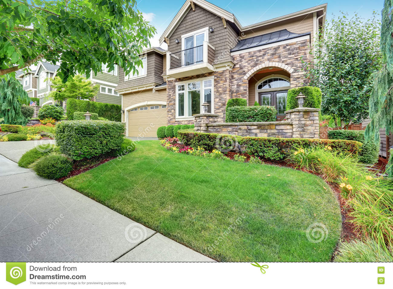 Red entrance door in front of residential house stock photo - Beautiful Curb Appeal Of Sweet Beige House With Green