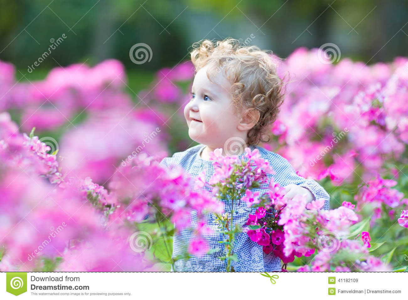 beautiful curly baby girl playing in the garden stock image - image
