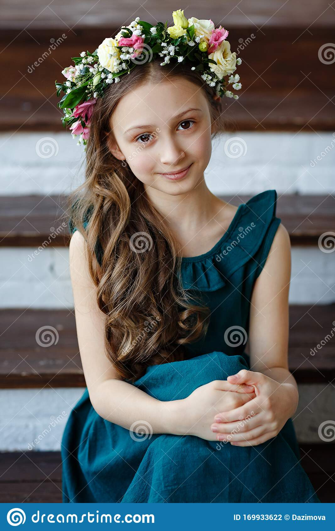Beautiful Cute Baby Girl With Long Hair In A Green Dress Sits In A Wreath  Of Fresh Flowers On Her Head And Looks At The Camera Stock Photo - Image of  baby,