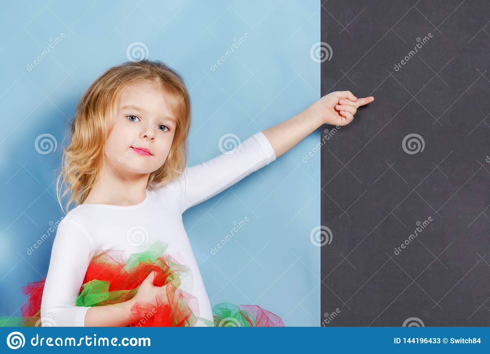Beautiful cute baby posed. A little girl with blond hair points her finger at a blank space on a black background.