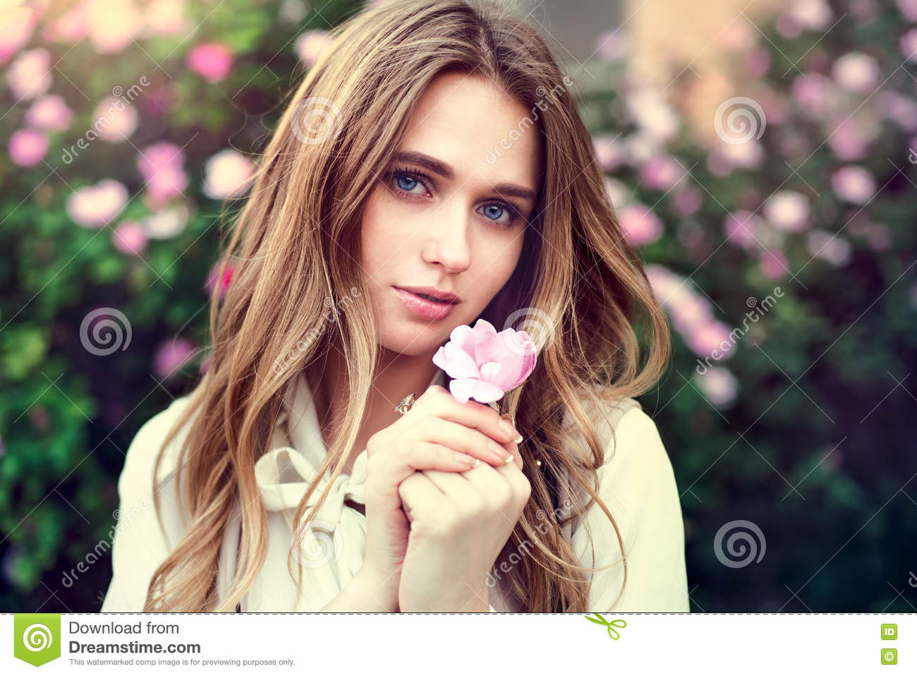 Beautiful cute girl holding rose flower in hands close to her face at sunset time