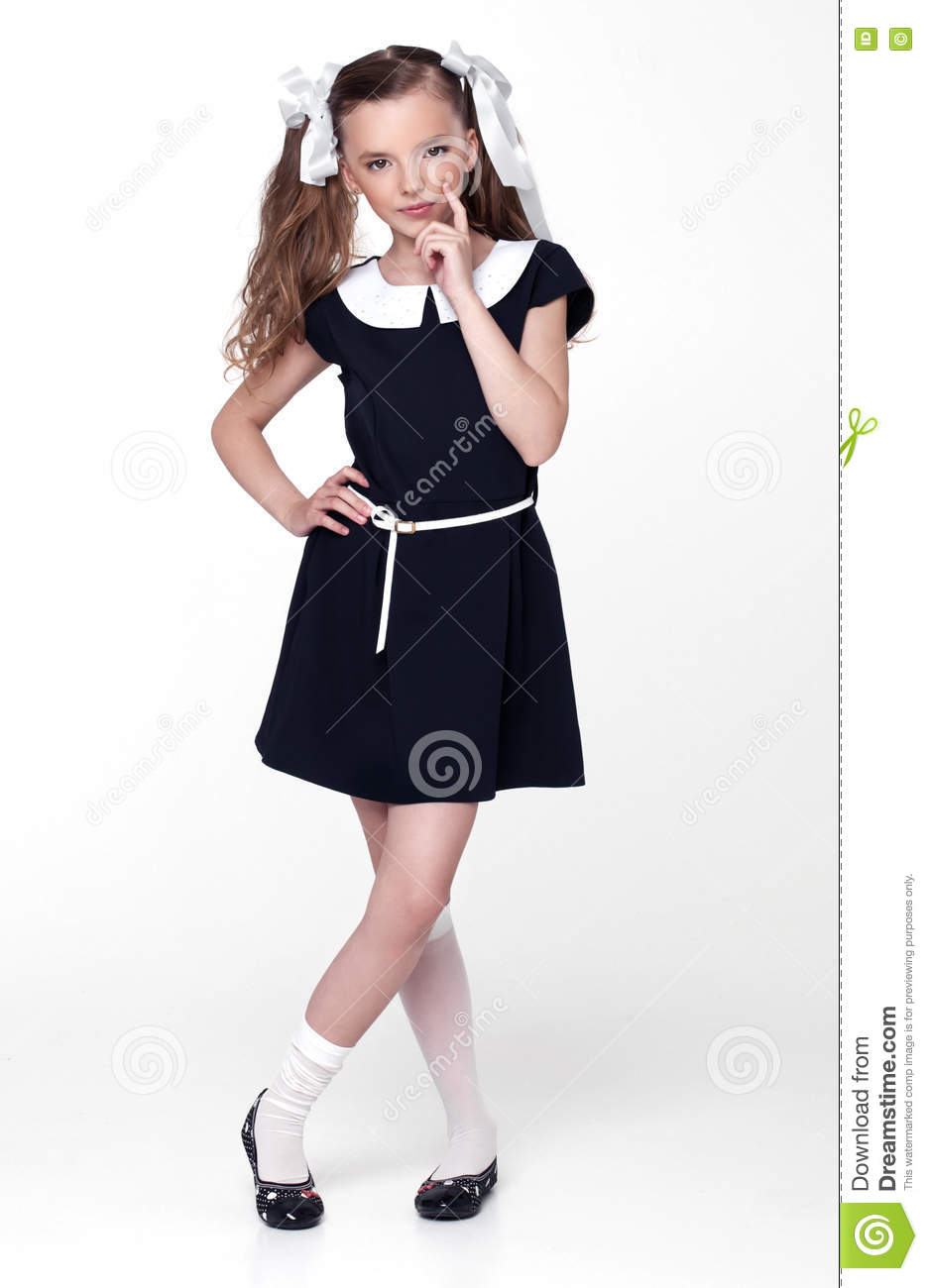Beautiful little girl in school uniform with books and