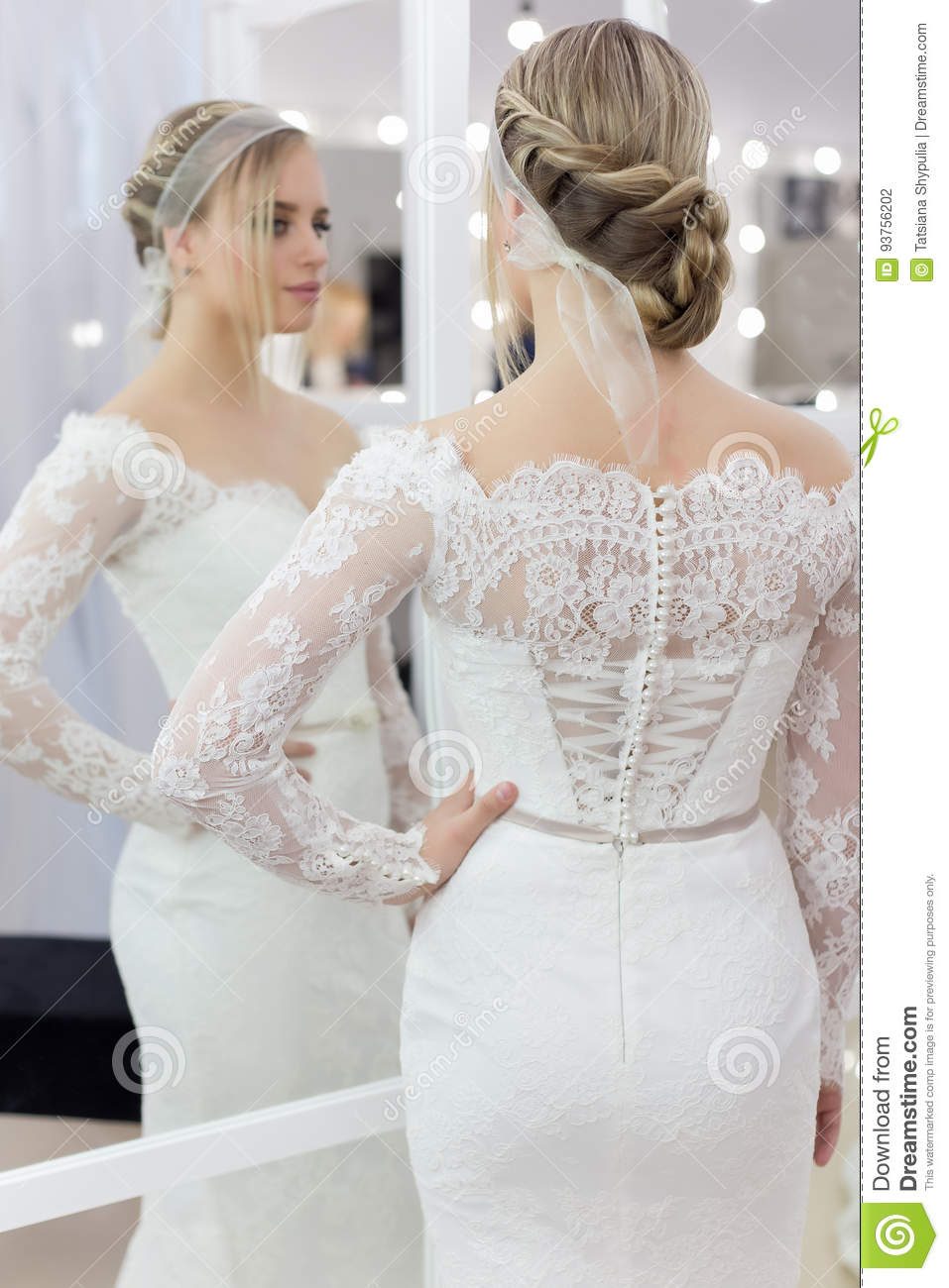 Beautiful cute tender young girl bride in wedding dress in mirrors with evening hair and gentle light make-up