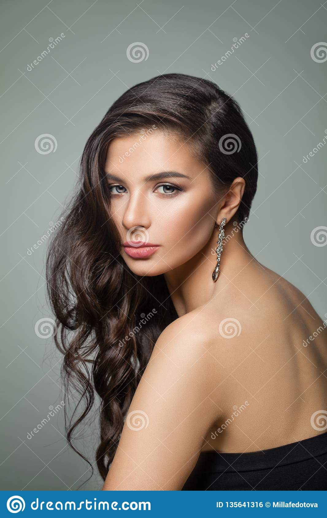 Beautiful dark brown hair woman. Fashion model with long perfect hairstyle, makeup and jewelry earrings