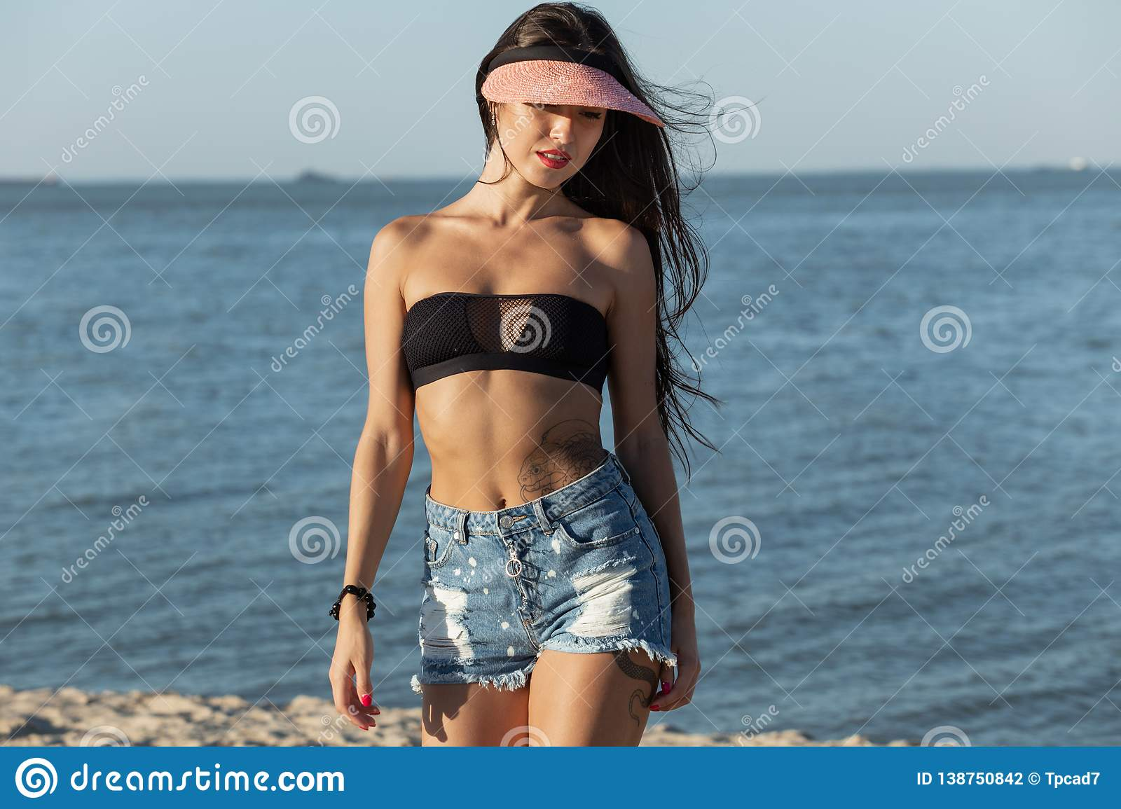 Beautiful dark-haired girl in sunglasses and cap dressed in a black bra and jean shorts is standing near the sea