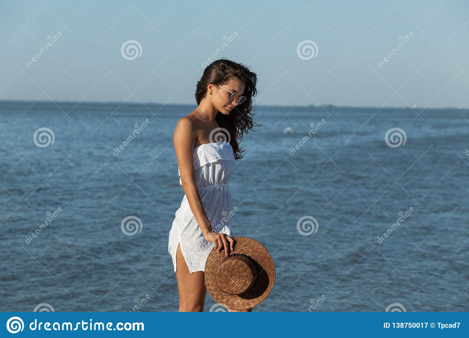 Beautiful dark-haired girl in white dress and sunglasses hold hat in hand and walk near the sea on a sunny day.