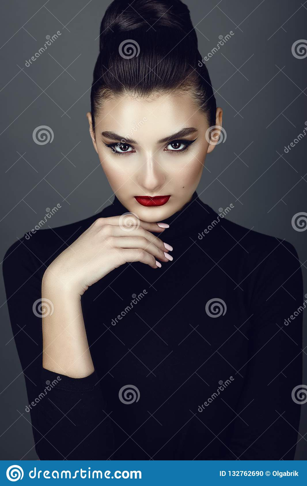 Beautiful dark haired model with perfect make up and her hair scraped back into a high bun leaning her chin on the hand