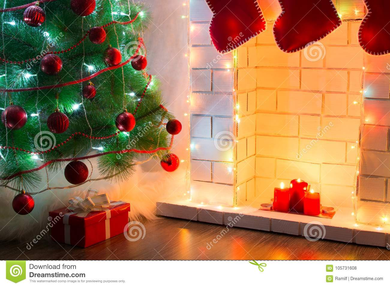 Beautiful decorated tree with presents on floor near fireplace with warm light of candles.