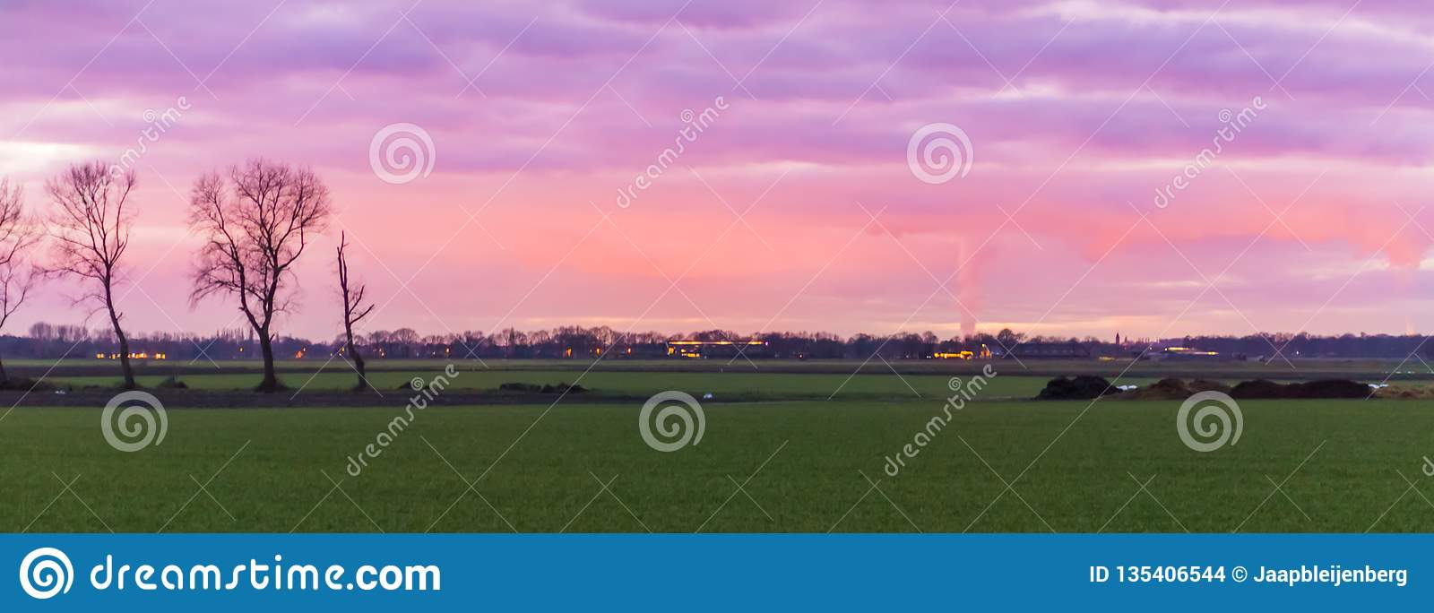 Beautiful dutch landscape of a grass field with buildings in the distance, nacreous clouds coloring the sky pink and purple, a