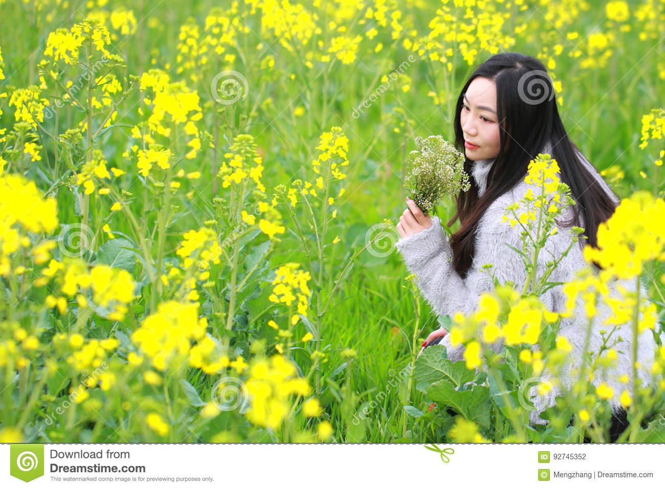At Beautiful Early Spring A Young Woman Stand In The Middle Of