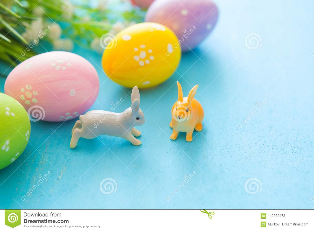 Beautiful Easter eggs with rabbits toy and flowers on blue wooden background, closeup. Easter holiday concept