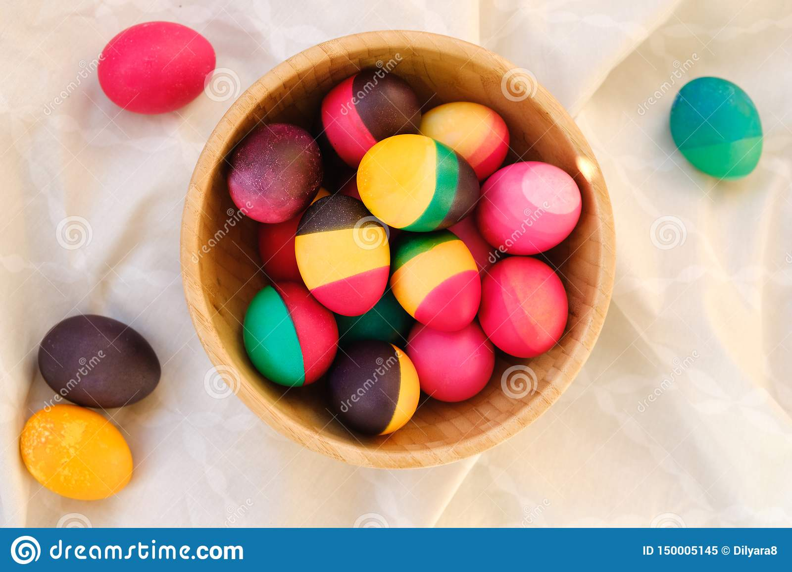 Decorative colorful Easter eggs in a wood bowl
