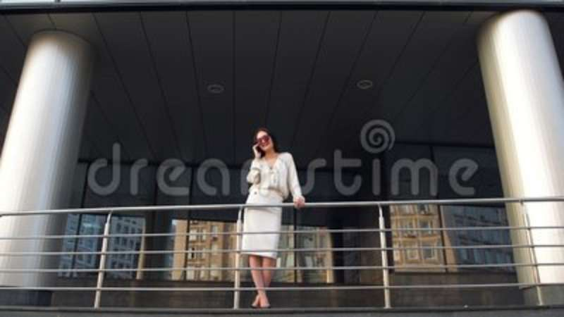 Beautiful elegant brunette businesswoman with mobile phone talking, smiling and laughing in front of skyscraper building. Footage was made with fullframe Nikon stock footage