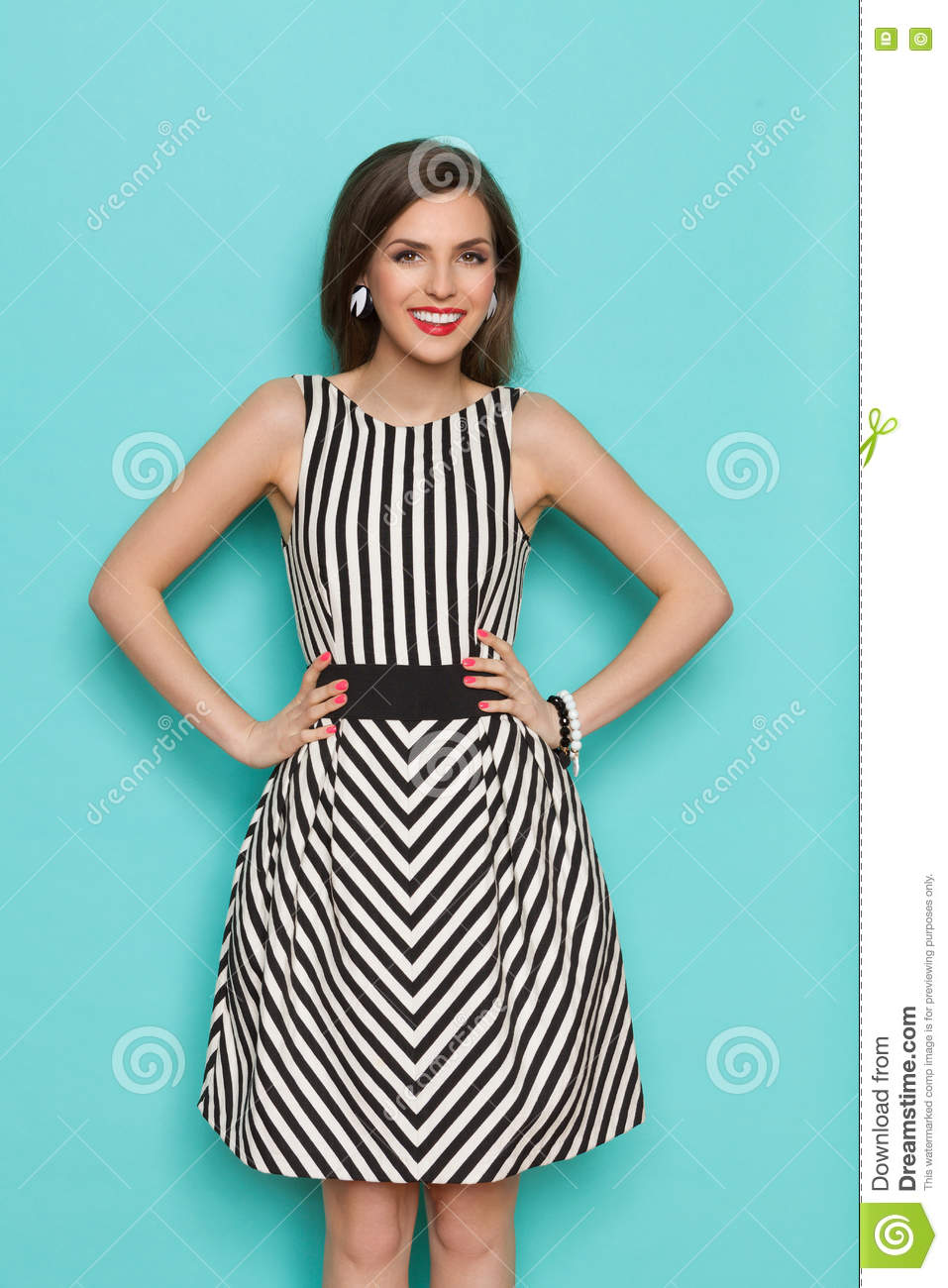 bfb678969fc Smiling elegant woman in black and white striped dress posing with hands on  hip and looking at camera. Three quarter length studio shot on turquoise ...