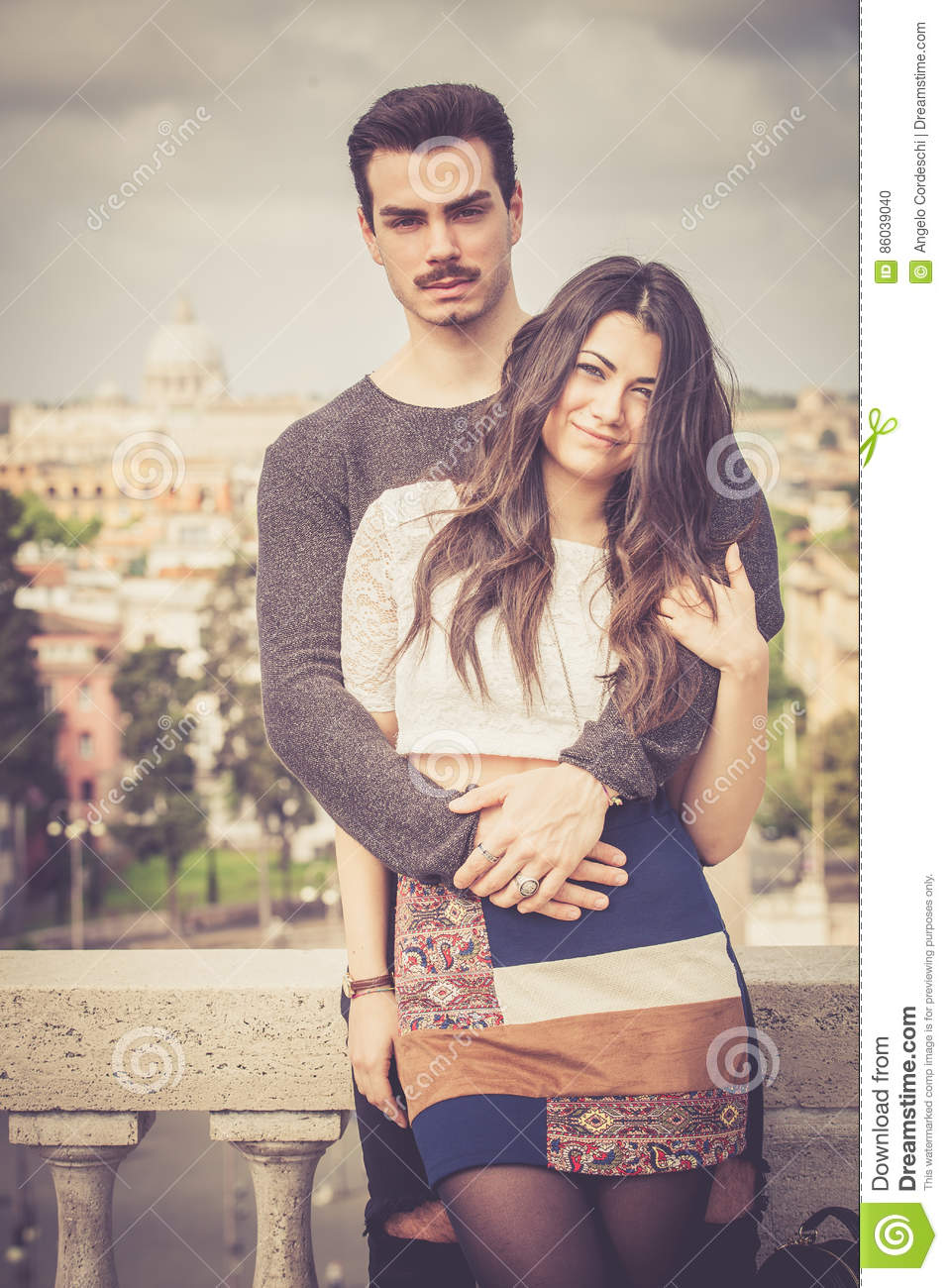 Beautiful embracing lovely young italian couple outdoors