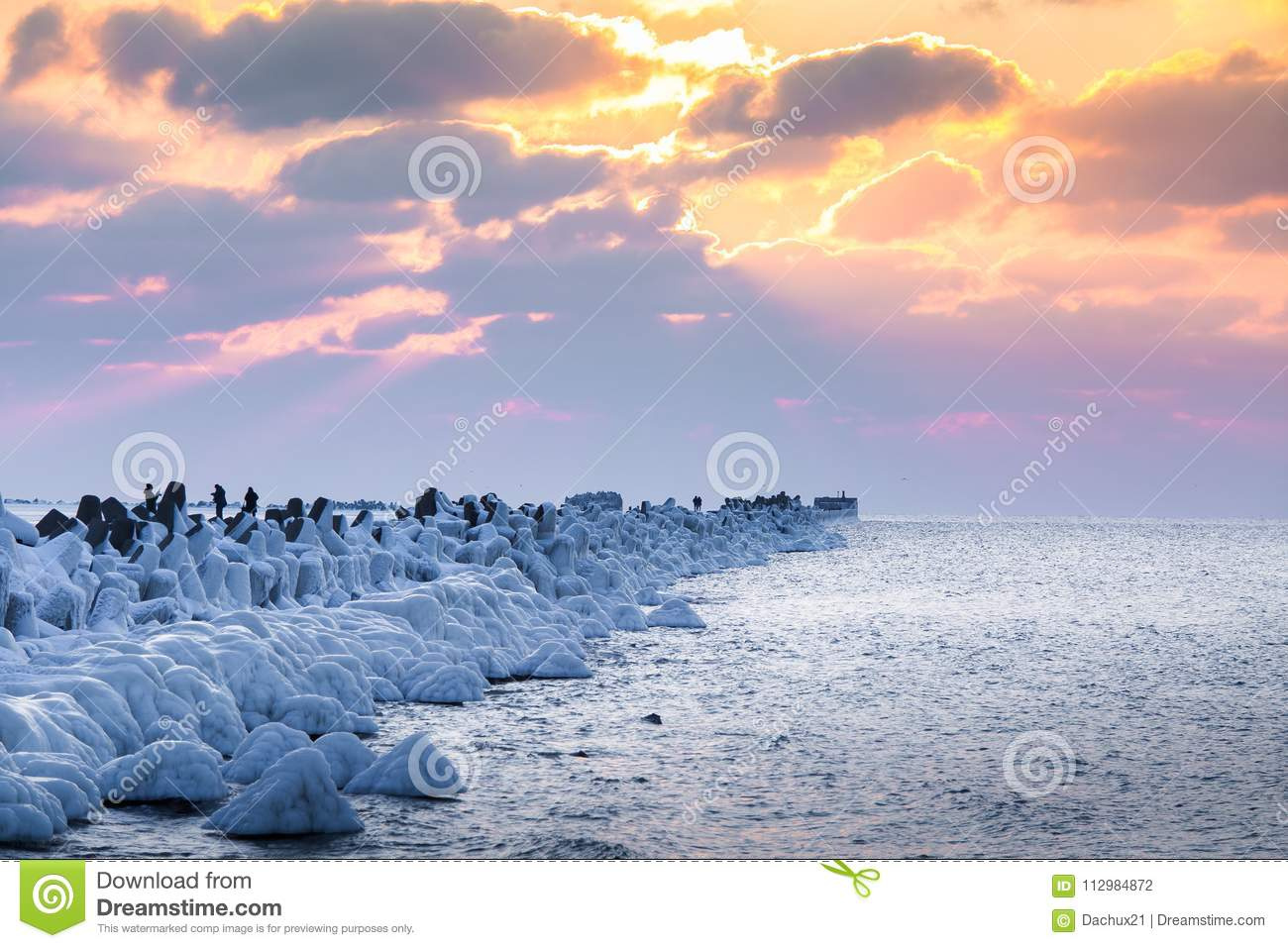 A beautiful evening landscape of a frozen breakwater in the Baltic sea. Winter landscape at the beach.