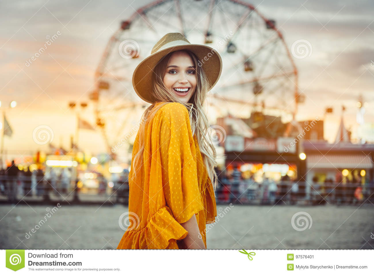 Beautiful exited smiling tourist woman having fun at amusement park at hot summer day trip on the beach