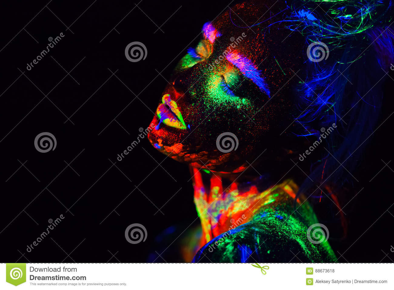 Beautiful extraterrestrial model woman in neon light. It is portrait of beautiful model with fluorescent make-up, Art