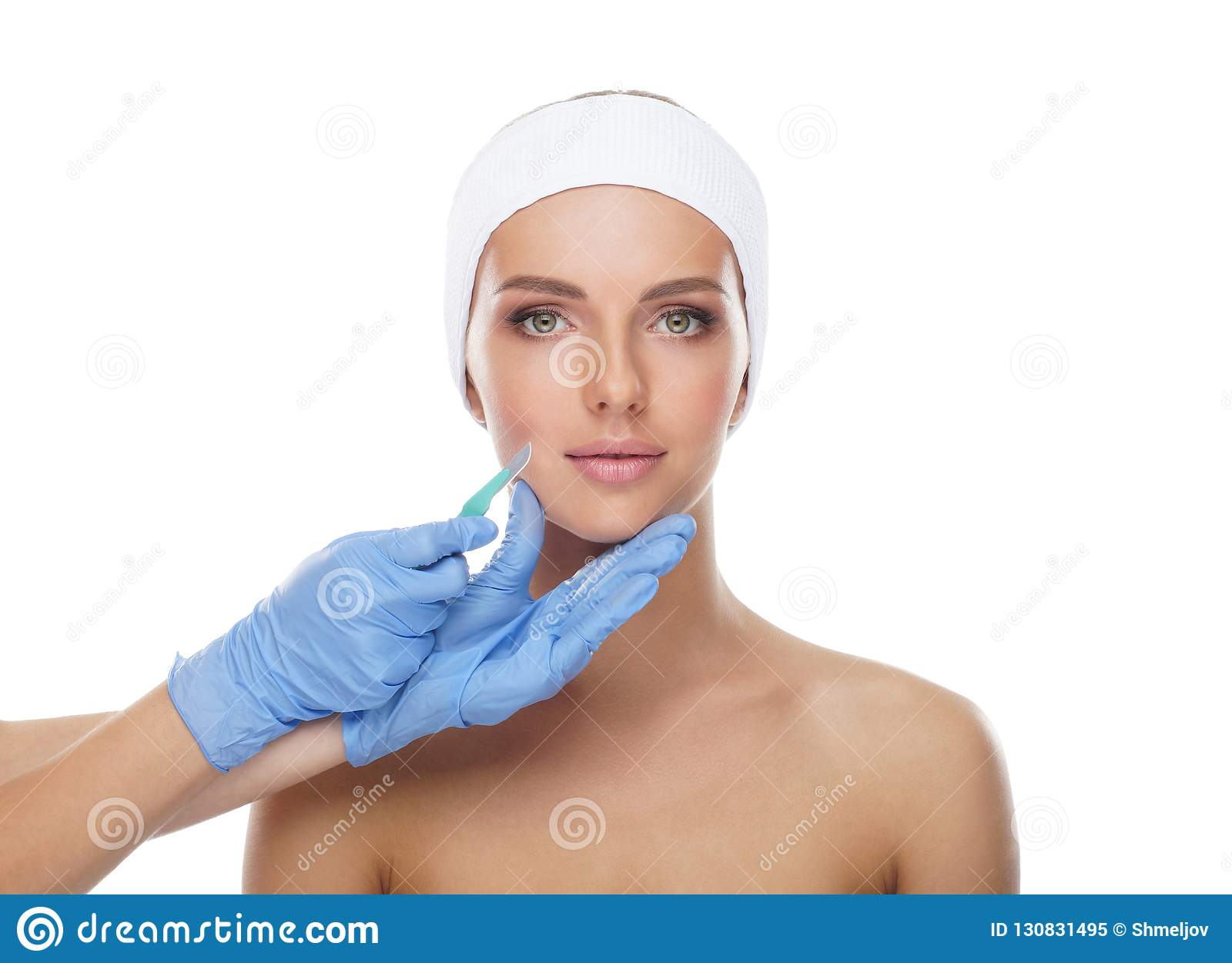 Beautiful face of the young woman and the medical scalpel in doctor`s hands isolated on white. Plastic surgery and face
