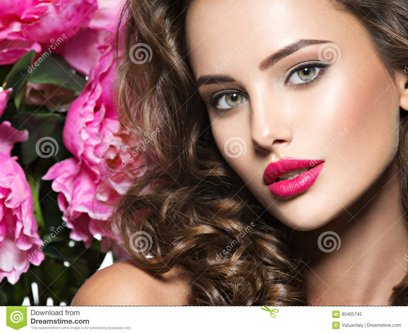 Beautiful Face Of Young Woman Over The Pink Flowers Stock Image