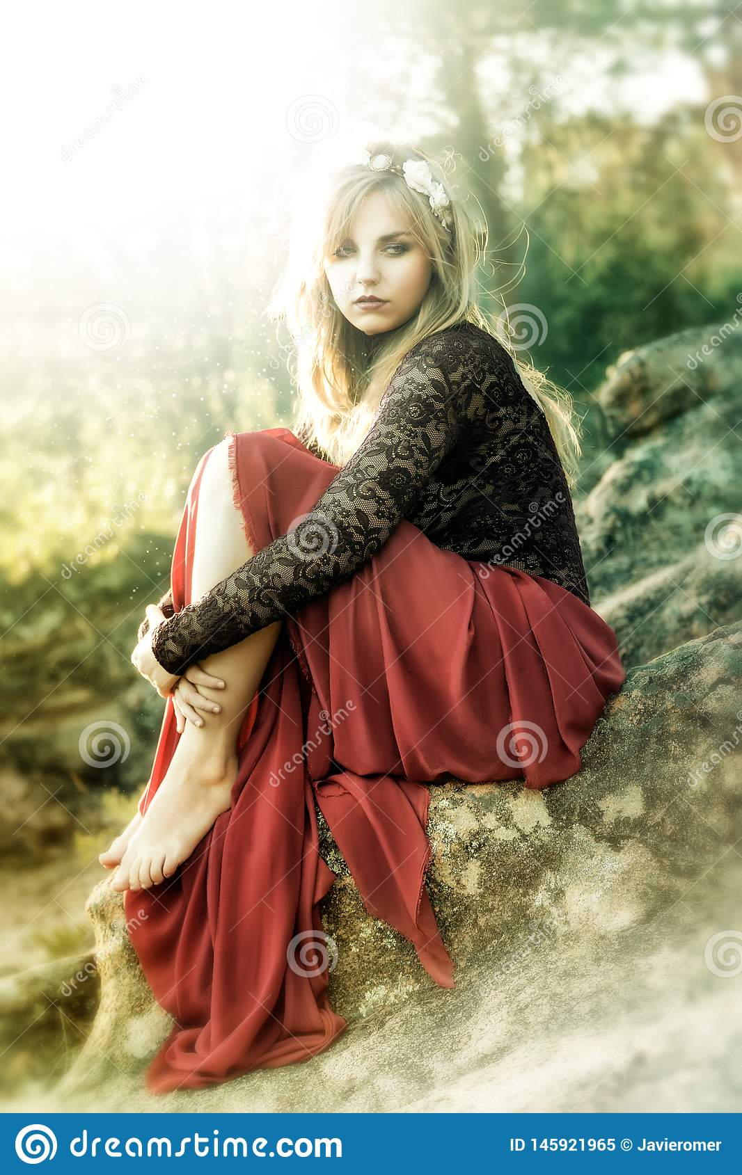 Beautiful fairy blonde dressed in a red sitting on the roccks.