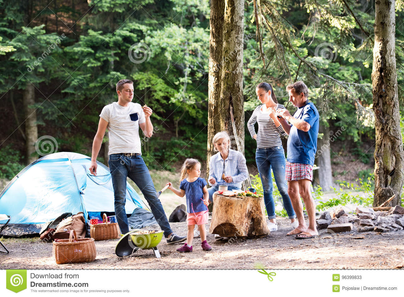Beautiful family camping in forest eating together