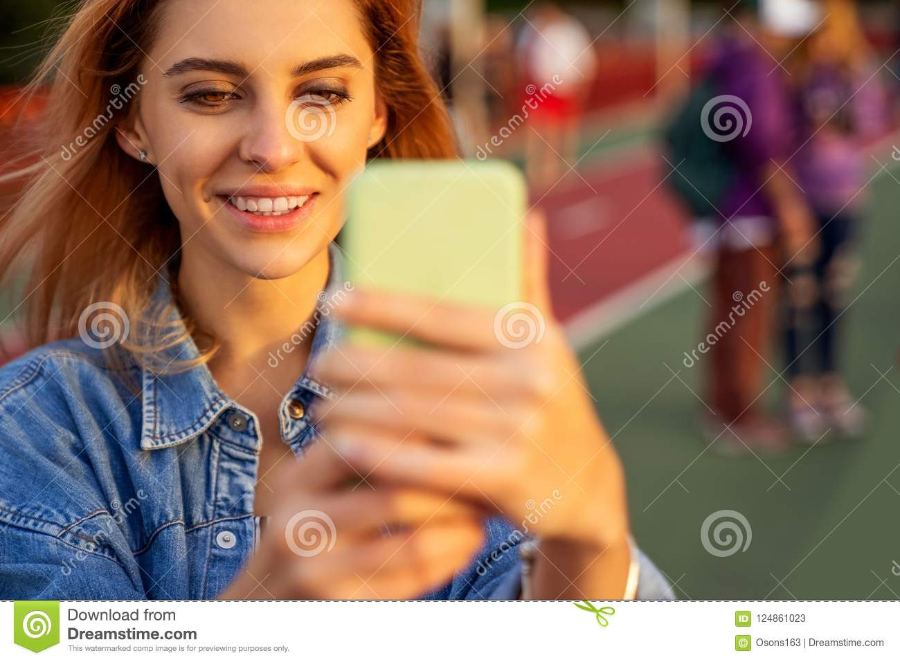 Beautiful fashion girl doing selfie with phone at sunset