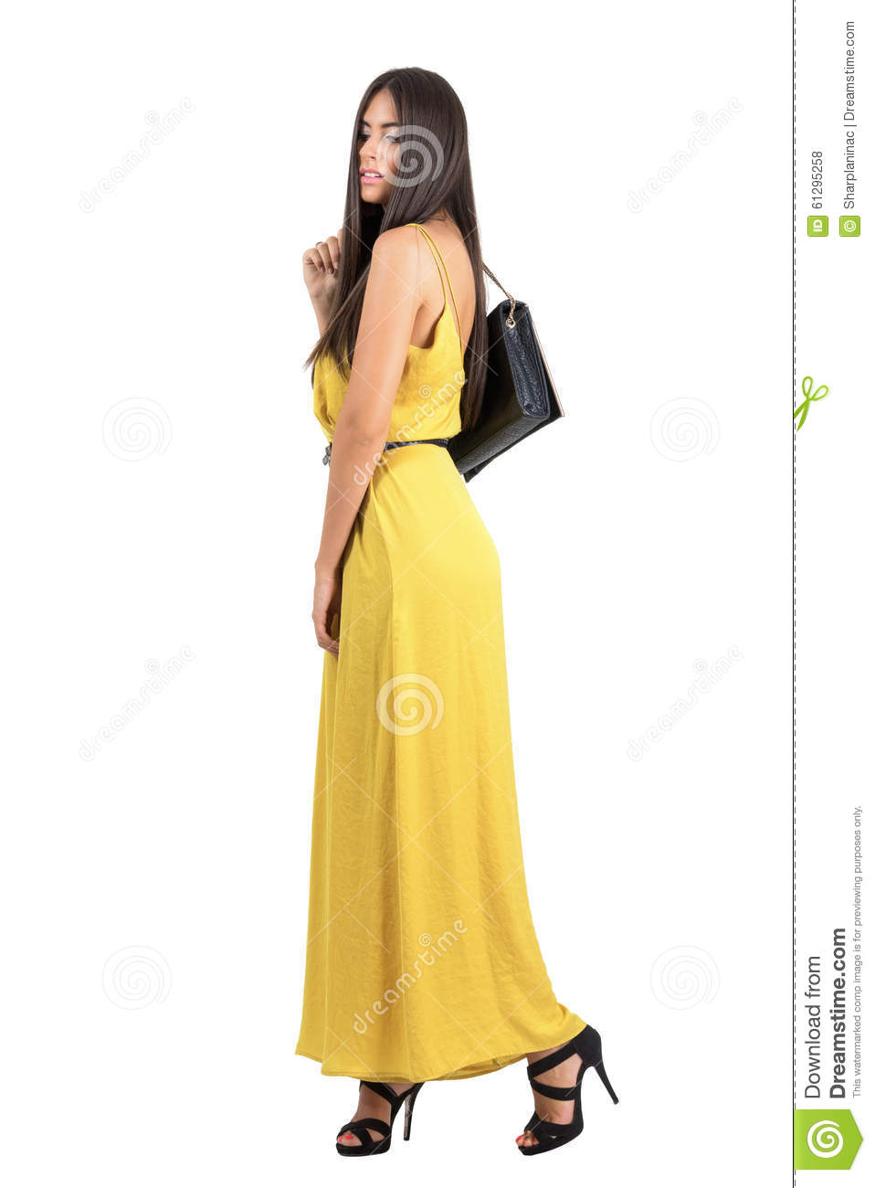 e7d224816a5a Beautiful fashion model in yellow jumpsuit walking with bag over the  shoulder. Full body length portrait isolated over white studio background.