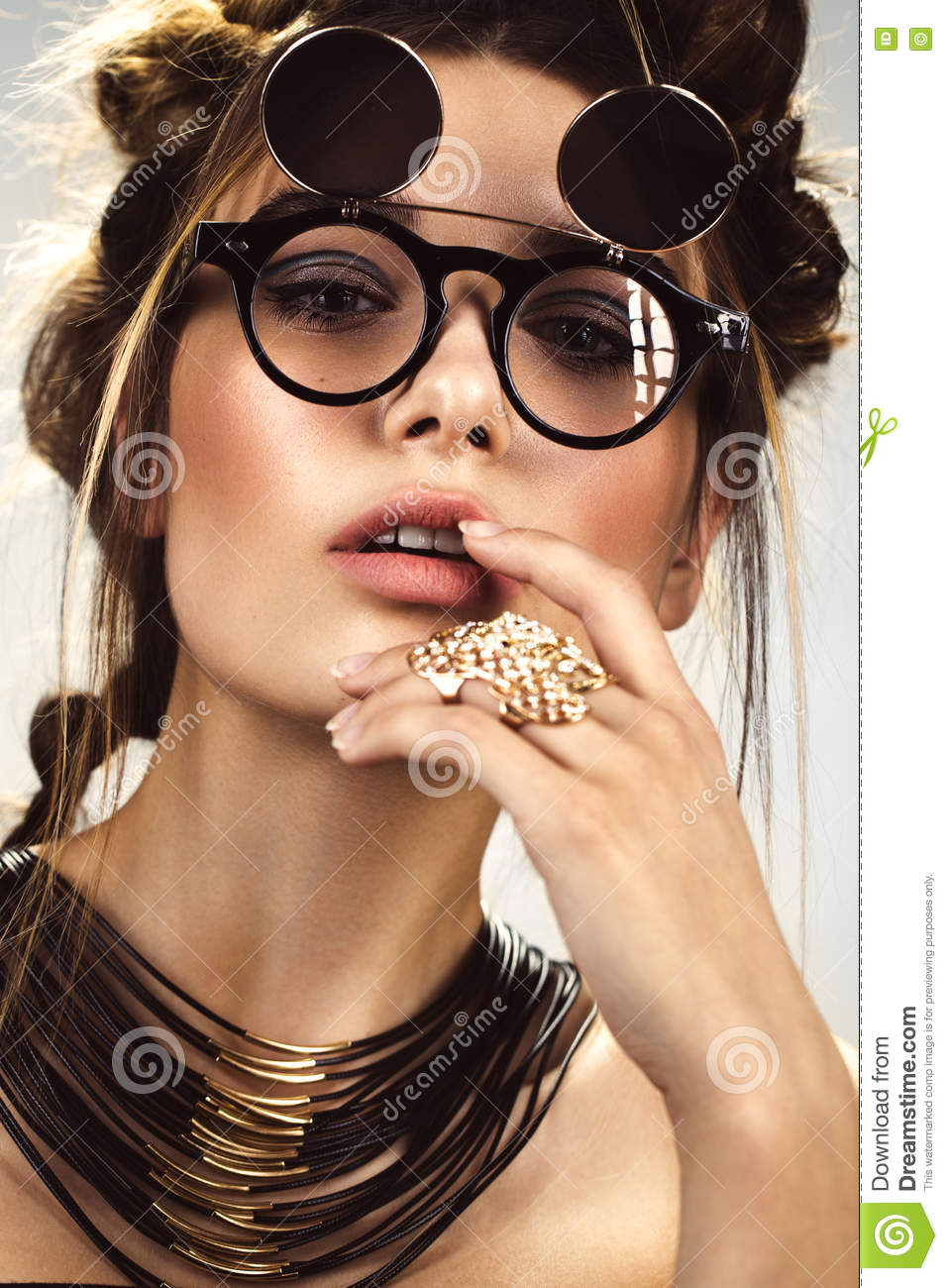 Beautiful fashion woman with creative make-up, hairstyle wearing glasses and jewelry. beauty face.