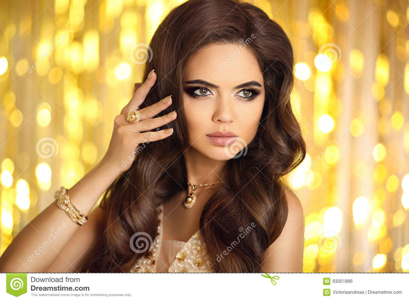 Beautiful fashion woman in gold. Elegant brunette with makeup, l