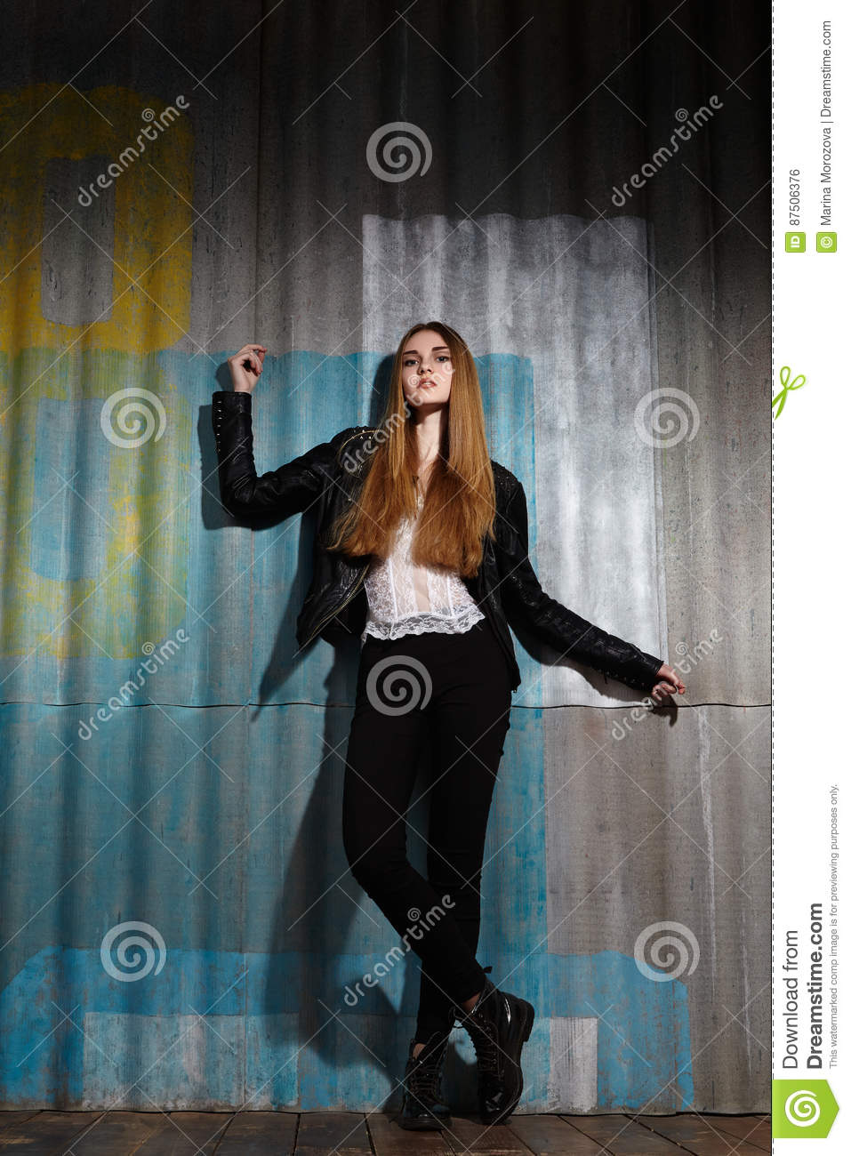 Beautiful fashion woman model in rock leather jacket, dark make-up. Street fashion look. Long hairstyle, straight hair
