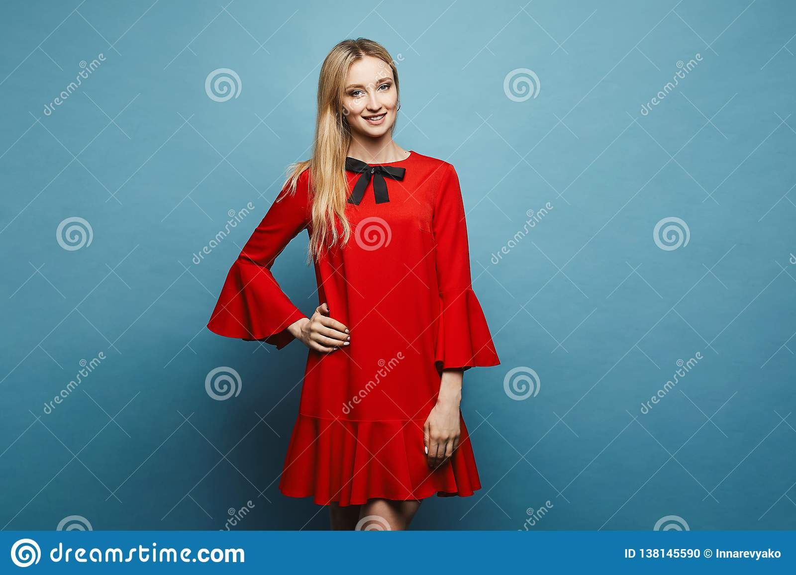 Beautiful and fashionable blonde model girl with perfect slim body in a stylish short red dress with black bow posing at