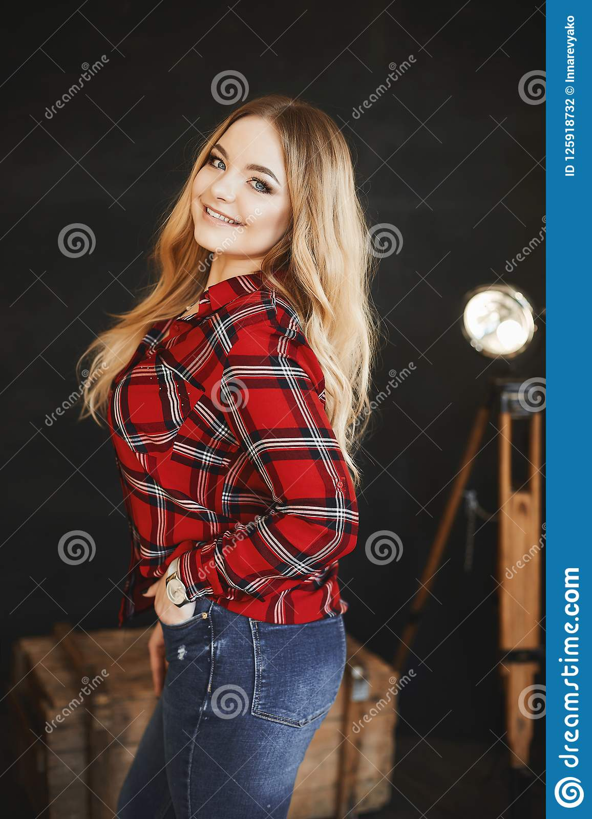 Beautiful and fashionable blonde pluss-size model girl with big breast in red plaid shirt and in a jeans, stands near the wooden c