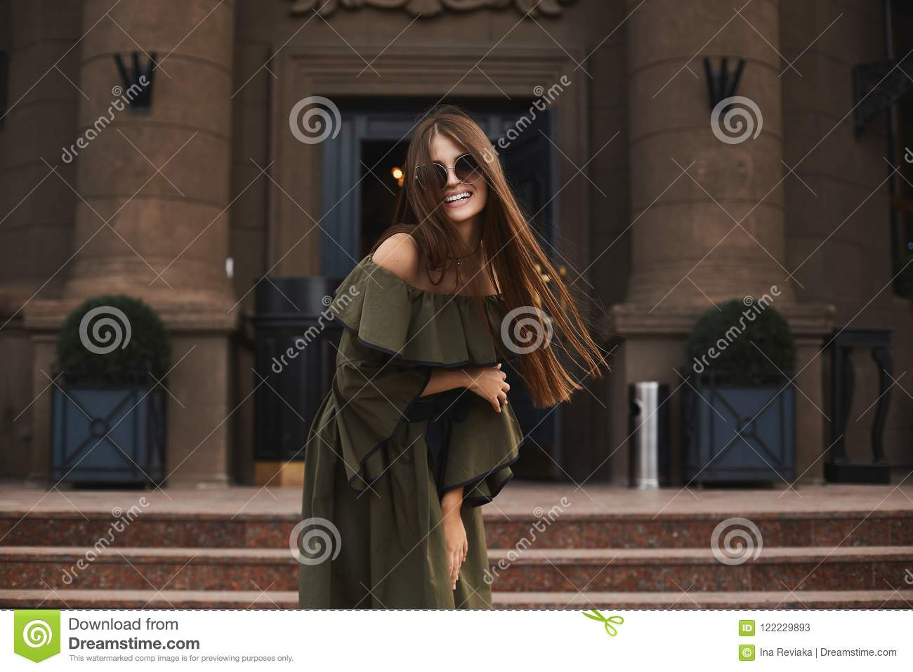 Beautiful and fashionable brunette model girl with charming smile, in stylish dress with naked shoulders and in the trendy sunglas