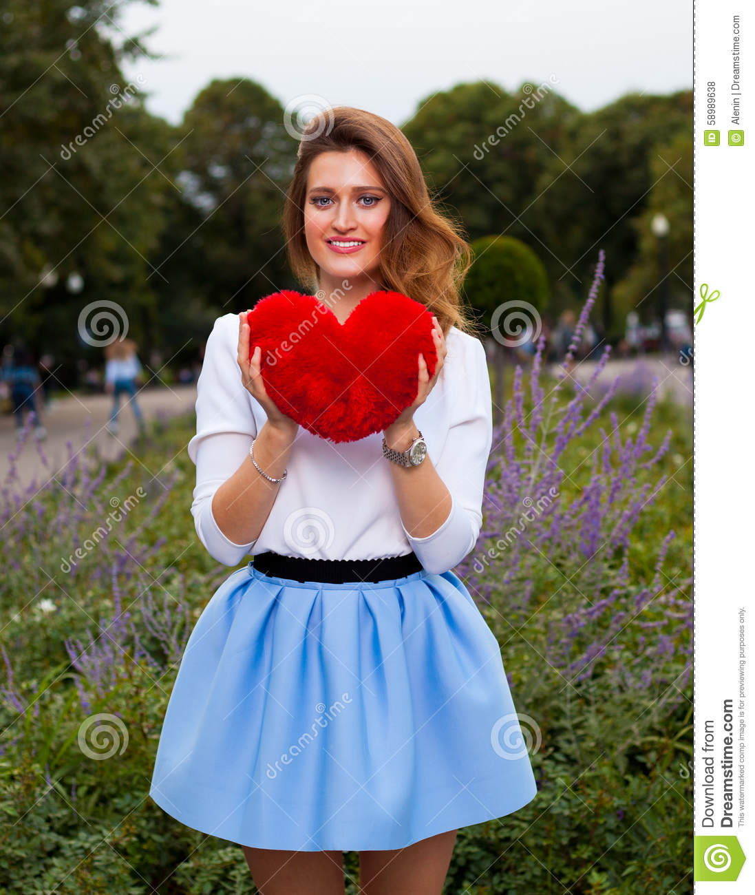 Beautiful fashionable Girl with red heart in the park in warm summer evening