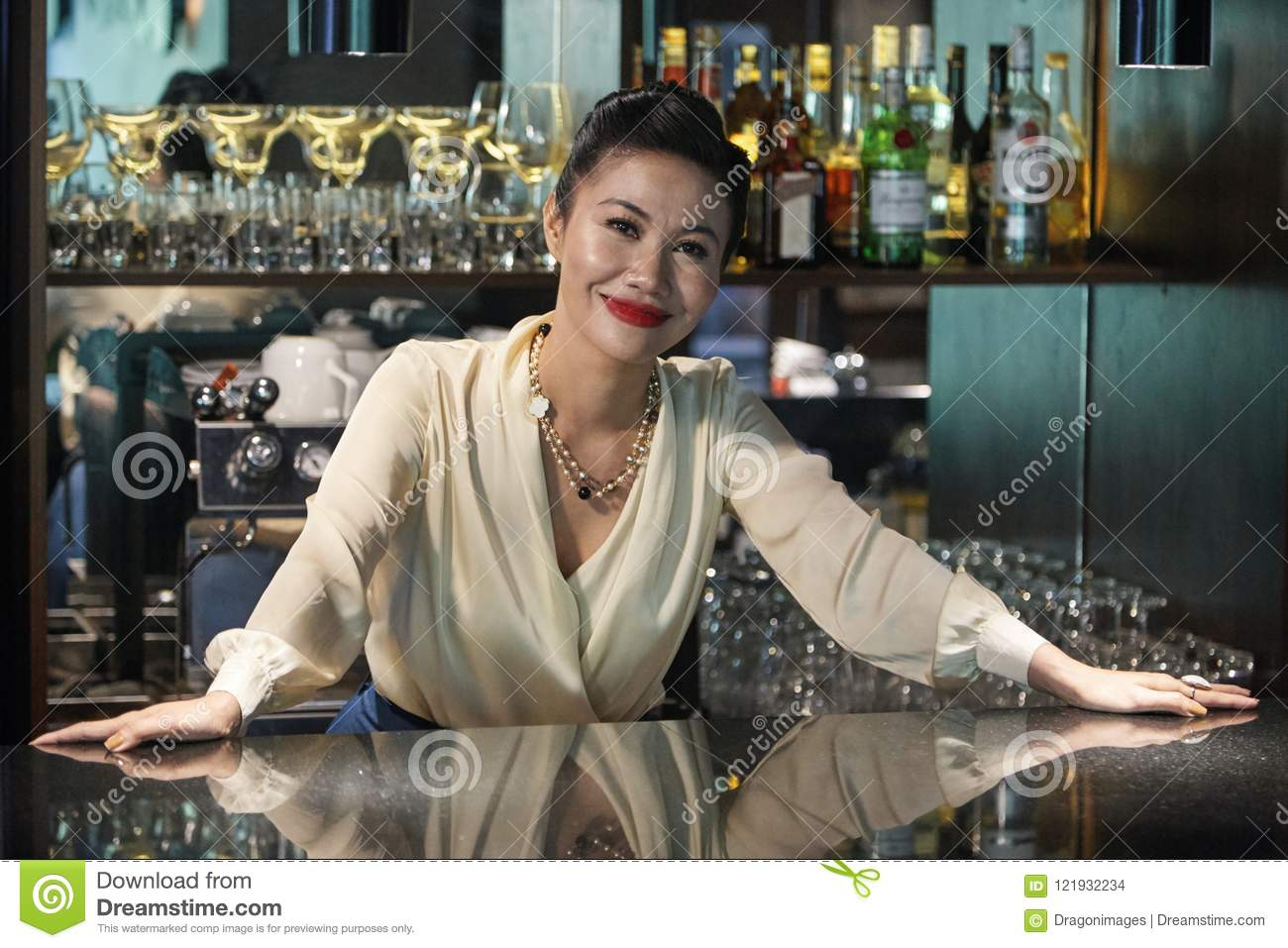Beautiful female bartender standing relaxed at counter
